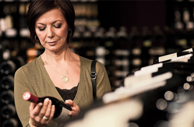 A lady hilds and examines a wine bottle while surrounded by racks of bottles