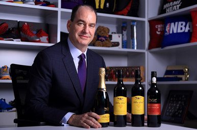 Robert Foye sitting with Wolf Blass wine bottles in front of shelves of NBA merchandise